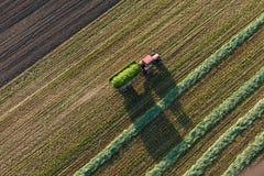Flyg- sikt av skördfält med traktoren royaltyfria foton
