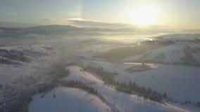 Flyg- sikt av snow-covered berg lantlig vinter för liggande Flyg över en by i Carpathian berg lager videofilmer