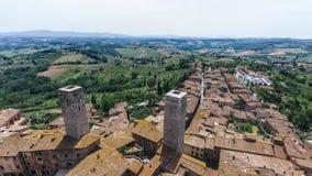 Flyg- sikt av staden av San Gimignano och Tuscan fält i den arkivfoto