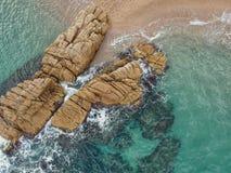 Flyg- sikt av stranden med klippan och havet i Costa Brava arkivbild