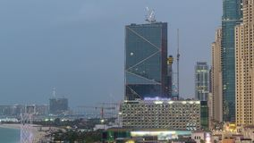 Flyg- sikt av stranden och turister som g?r i JBR med skyskrapadag till natttimelapse i Dubai, UAE stock video