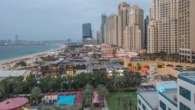 Flyg- sikt av stranden och turister som g?r i JBR med skyskrapadag till natttimelapse i Dubai, UAE lager videofilmer