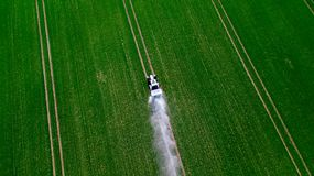 Flyg- sikt av traktoren som besprutar kemikalieerna p? det stora gr?na f?ltet arkivfoton