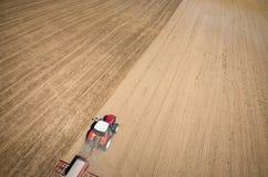 Flyg- sikt av traktoren som harvar fältet Fotografering för Bildbyråer