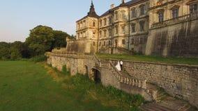 Flyg- sikt av unga brölloppar som går på trappa till den gamla antika slotten i 4k stock video