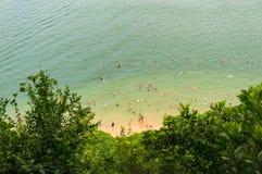Flyg- sikt av unidentifiable folk som simmar på stranden arkivbild