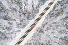 Flyg- sikt av vägen med den röda lastbilen i vinterskog Arkivbilder