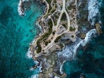 Flyg- sikt av vågor som kraschar på Punta Sur - Isla Mujeres, Mexico - med briljant blått vatten och att krascha vågor och stenig arkivfoto