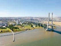 Flyg- sikt av Vasco da Gama Bridge And High biltrafik i den Lissabon staden Arkivfoto
