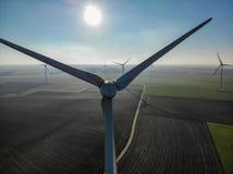 Flyg- sikt av vindturbiner och jordbruks- fält på en härlig blå vinterdag royaltyfri bild