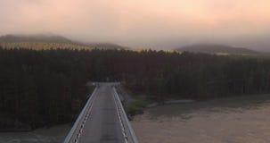 flyg- sikt Bron över bergfloden, som är fött över, och flöten fördunklar 4K stock video