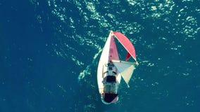 flyg- sikt Den härliga segla yachten med ett rött seglar seglar på smaragdhavet på en solig dag stock video