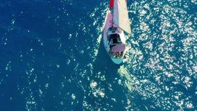 flyg- sikt Den härliga segla yachten med ett rött seglar seglar på smaragdhavet på en solig dag lager videofilmer