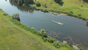 flyg- sikt En liten gummifiskebåt med en motor flyttar sig snabbt på en liten flod lager videofilmer