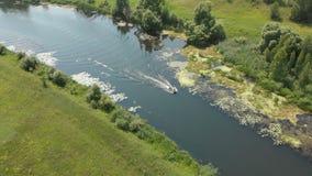 flyg- sikt En liten gummifiskebåt med en motor flyttar sig snabbt på en liten flod stock video