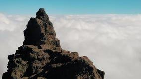 flyg- sikt Ett ungt par står på kanten av klipporna ovanför molnen Kameran flyttar sig till en stor klippa över arkivfilmer