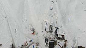 flyg- sikt för öga för fågel 4k av skidåkaregrunden med kabelvägen och parachuter, fjällängar arkivfilmer