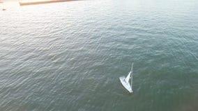 Flyg- sikt för hög vinkel av yachtseglingen i väg från kust på en ljus solnedgång med soliga signalljus och strålar lager videofilmer