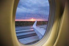 Flyg- sikt för soluppgång till och med affärsstrålfönster över vingar Arkivfoton