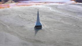 flyg- sikt för surr 4k av den översvämmade och övergav kyrkan i mitt av en sjö som förorenas med cyanid arkivfilmer