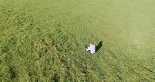 Flyg- sikt för UHD 4K Lågt orbitalflyg över affärsmansammanträde på grönt gräs med anteckningsbokblocket på fältet lager videofilmer