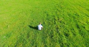 Flyg- sikt för UHD 4K Lågt orbitalflyg över affärsmansammanträde på grönt gräs med anteckningsbokblocket på fältet stock video