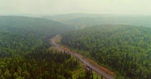 Flyg- sikt f?r panorama p? v?gen i flyg- sikt f?r skog av dumpers p? landsv?gen i skogsikt fr?n surret p? taigaen lager videofilmer