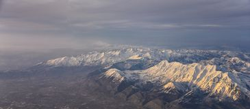 Flyg- sikt fr?n flygplanet av Wasatchen Front Rocky Mountain Range med korkade maxima f?r sn? i vinter inklusive stads- st?der av royaltyfri foto