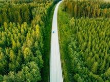 Flyg- sikt från ovannämnt av landsvägen till och med den gröna sommarskogen i sommar Finland royaltyfri foto