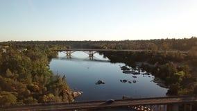 Flyg- sikt från surret som flyger över floden och den ärke- bron Kalifornien USA stock video