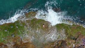 flyg- sikt Havsvågor som plaskar med skum och sprej till den härliga kvinnan för den steniga kusten, ligger på den steniga strand lager videofilmer