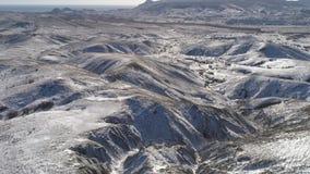 Flyg- sikt i bergskedjor och kullar som täckas av snö nära havet skjutit underbar liggande stock video