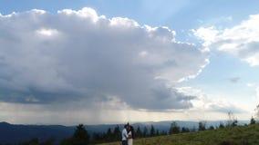 flyg- sikt 4K Mannen och kvinnan rymmer sig händer som står på kullen under tunga moln över bergen lager videofilmer