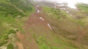 Flyg- sikt Kamchatka Flyga över stenarna och snön flyg in i dimman lager videofilmer