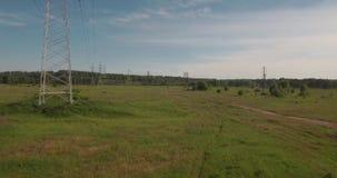 flyg- sikt lantlig väg bland fält och elektrisk hög-spänning service bygdväg mellan det gröna fältet 4K lager videofilmer