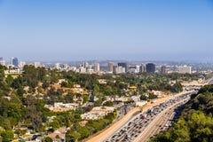 Flyg- sikt in mot horisonten av den Westwood grannskapen; huvudväg 405 med tung trafik i förgrunden; Los Angeles arkivbild