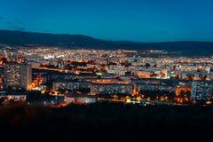 Flyg- sikt, nattcityscapesikt med natthimmel naturlig klar sikt över storstadkvarter med gataljus och kullar omkring - royaltyfria bilder