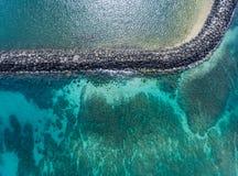 Flyg- sikt ovanför havet och vågbrytaren Arkivbild