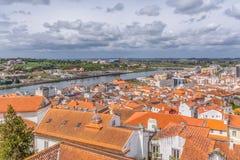 Flyg- sikt på den Mondego floden och banker med den Coimbra staden, himmel med moln som bakgrund, i Portugal arkivfoto