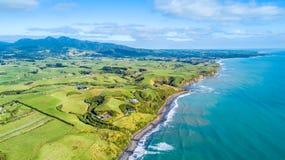 Flyg- sikt på den Tasman kusten med lantgårdar och materielpaddockar Taranaki region, Nya Zeeland royaltyfria bilder