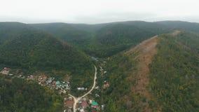 Flyg- sikt på en by i kullarna arkivfilmer