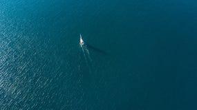 Flyg- sikt på en yacht som springer längs det mycket lilla öhavet på solig dag Coromandel halvö, Nya Zeeland Royaltyfri Fotografi