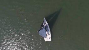 Flyg- sikt på ensam sjöman på djupblått vatten Ett ensamt fartyg på floden Flyg- sikt av gröna öar och moln på stock video