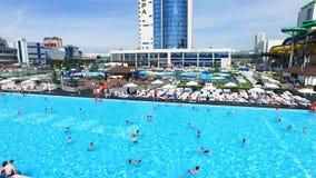 Flyg- sikt på folk som simmar i pöl vid det lyxiga hotellet, bakgrund av krusigt vatten i simbassäng och trä arkivfilmer