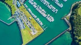 Flyg- sikt på ingången till marina med fartyg som vilar längs pir och bilarna som väntar på parkeringsplatsen Auckland nytt Z Royaltyfri Bild