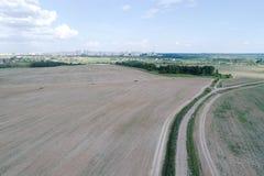 Flyg- sikt på jordbruks- fält med den lantliga vägen across Royaltyfri Fotografi
