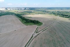 Flyg- sikt på jordbruks- fält med den lantliga vägen across Royaltyfria Bilder