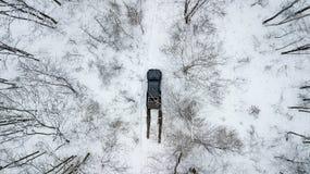 Flyg- sikt på SUV 6x6 som rider vid vintervägen i snö-täckt skog Arkivfoto