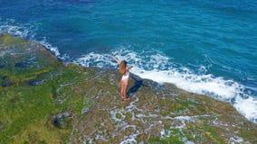 flyg- sikt Sexigt flickaanseende på klippan på Rocky Beach En kvinna ser in i avståndet stock video