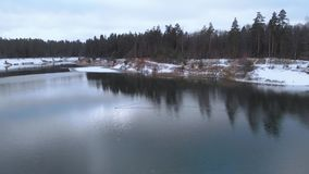 flyg- sikt Sjön i vinterskogflyget över en inte djupfryst sjö i molnigt vinterväder Färgrikt landskap, frostig helgdagsafton lager videofilmer